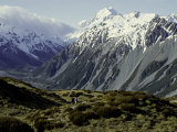 Hikers Look up at Snowy Mountain Top, New Zealand Photographic Print by Michael Brown
