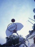 Low Angle View of a Basketball Above a Hoop Photographic Print