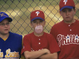 Three Boys on a Baseball Team Standing Against a Chain-Link Fence Photographic Print
