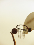 Person's Hand Holding a Basketball Near the Hoop Photographic Print