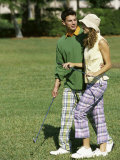 Mid Adult Man and a Mid Adult Woman Walking on a Golf Course Photographic Print