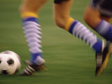 Low Section View of a Soccer Player Running with a Soccer Ball Photographic Print