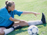 Teenage Girl Stretching on a Lawn Photographic Print