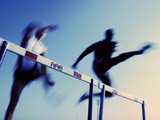Low Angle View of Athletes Jumping over Hurdles Photographic Print
