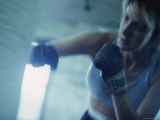Female Boxer Punching a Punching Bag Photographic Print