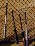 Baseball Bats Resting Against a Chain-Link Fence Photographic Print