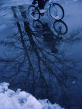 Puddle Reflecting a Passing Bicyclist Photographic Print
