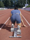 Rear View of a Female Athlete in The Starting Position on a Running Track Photographic Print