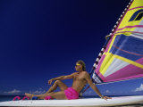 Young Man Sitting on a Surfboard at the Beach Photographic Print