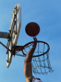 Low Angle View of a Person's Hand Shooting a Basketball into The Hoop Photographic Print