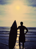 Silhouette of a Man Holding a Surfboard Standing on the Beach Photographic Print
