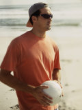 Young Man Holding a Volleyball on The Beach Photographic Print