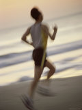 Rear View of a Mid Adult Man Jogging on the Beach Photographic Print