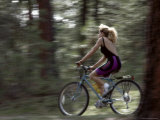 Woman Bicycling Through Trees Photographic Print