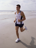 Young Man Jogging on the Beach Photographic Print