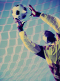 Low Angle View of a Goalie Catching a Ball Lámina fotográfica