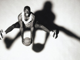 Portrait of a Young Man Holding a Basketball Jumping Up in The Air Photographic Print