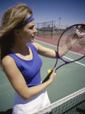 Young Woman Holding a Tennis Racket Standing Near a Net Photographie