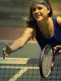 Young Woman Reaching Out over a Net at the Tennis Court Photographie
