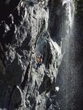 Rock Climber Near a Waterfall Fotografisk tryk