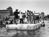 Several Young Men and Women on a Platform in the Water, Some of Them Dancing, on the Lido of Venice Lámina fotográfica