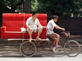 A Chinese Man Rides on a Sofa as Another Pedals a Delivery Tricycle Photographic Print