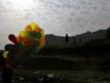 A Boy Walks as Selling Balloons in a Neighborhood in Kabul, Afghanistan, Thursday, August 24, 2006 Photographic Print by Rodrigo Abd