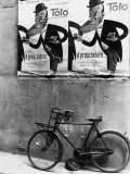 A Bicycle Leaning Against a Wall Photographic Print