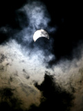 The Moon Partially Covers the Sun Behind the Clouds During a Partial Solar Eclipse Photographic Print