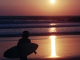 A Surfer is Silhouetted by the Setting Sun as He Leaves the Pacific Ocean on Venice Beach Photographic Print