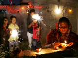 A Woman Lights Earthen Lamps as Children Ignite Firecrackers in New Delhi Photographic Print by Manish Swarup