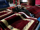 A Masked Boy Rests at a Carpet Shop in Kabul, Afghanistan, Friday, September 22, 2006 Photographic Print by Rodrigo Abd
