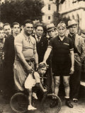 Two Cyclist Pose with a Little Boy Riding a Small Bike Behind Them, a Group of Men Photographic Print