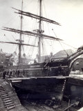 Close-Up of a Sailing Ship in a Dockyard Situated Among Buildings. a Few Workmen Can be Seen Photographic Print
