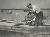 A Hungarian Fisherman, Standing up on a Boat, Weighs Some Fish with a Steelyard Photographic Print