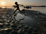 A Boy Plays on the Banks of the River Brahmaputra in Gauhati, India, Friday, October 27, 2006 Photographic Print by Anupam Nath