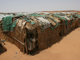 Two Sudanese Boys Stand by Makeshift Huts Photographic Print