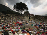 A Pakistani Refugee Walks Past Clothing Left Strewn on the Ground Photographic Print
