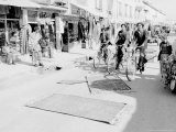 Rugs Get Instant Antiquing Treatment from Bicycle Riders Which Helps Make the Price Go Up Photographic Print
