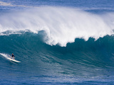 A Surfer Rides a Wave at Waimea Beach Photographic Print