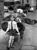 A Boy Gives a Ride to a Little Girl and a 9-Foot Teddy Bear at the Opening of the British Toy Fair Photographic Print