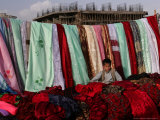 A Boy Rests on Textiles at a Street Stall Photographic Print