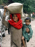 A Woman Carries Relief Supplies at Jula Village, Near Uri, India Photographic Print
