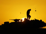 A U.S. Soldier Walks Atop His Armored Vehicle at Sunset Photographic Print