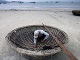 A Vietnamese Fisherman Does Repairs on His Basket Boat on a Beach Photographie