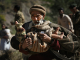 An Elderly Pakistani Earthquake Survivor Rushes Towards a Helicopter Carrying a Child in His Arms Photographic Print