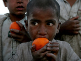 Refugee Boys Eat Tangerines at a Small Refugee Camp Photographic Print
