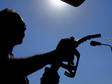 An Employee of a Petrol Station Holds a Petrol Pump after Filling up a Car Photographic Print
