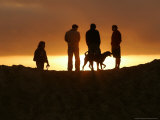 Bystanders Stand on a Berm During Sunset Photographic Print