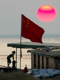 A Girl Rests on a Boat Below the Chinese National Flag Photographic Print